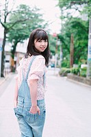 Japanese girl whit hands in her pockets looking at camera