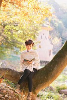 Japanese woman in a white cardigan reading a book sitting on a tree