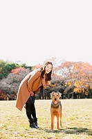 Japanese woman with long hair and a dog in a park looking at camera