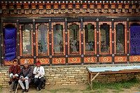 Asia, Bhutan, Thimphu. Three men sit on a bench at the Memorial Chorten in Thimphu.