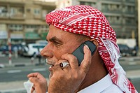 Arab man using mobile phone at the Docks, The Creek, Dubai, United Arab Emirates, Middle East