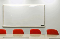 medium shot of white dry erase board and red chairs at conference table