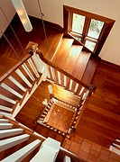 looking down three flights of stairs with a stair case made of hard wood.