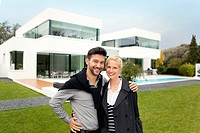 Couple smiling outside of modern luxury house, portrait