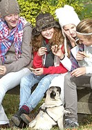 Girls and pet dog having picnic