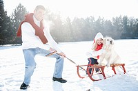 father pulling daughter and pet dog on sledge in snow