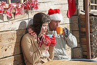Couple enjoying hot drink outside cabin at ski resort