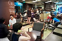 A busy coffee shop with young customers showing the increasing modernity of China