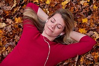 Young woman listening to music lying on a lawn of leaves