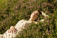 Young woman lying on a heather carpet