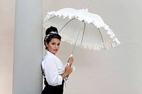 Young woman with an updo hairstyle, wearing a white shirt and holding a white umbrella