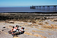 Two people lay on recliners on the beach at Cleveden