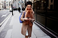 An elegant woman looks at her mobile phone as she walks through The City in London