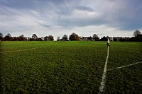 A lone man walks across a football pitch in The Downs area of Bristol