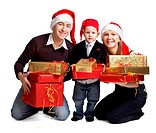 Isolated studio shot of happy young family of three wearing smart casual clothes and Santa's hats with a lot of Christmas presents.