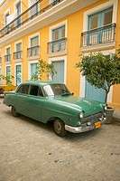 Russian car in Old Havana, Cuba with yellow building in background
