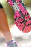 Close shot of the sole of a running shoe on a woman running through a forest