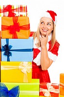 Young blond happy cute woman in Santa costume surrounded by Christmas gift boxes, isolated on white background