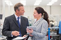 Businessman and businesswoman meeting in manufacturing plant