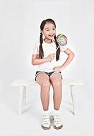 Smiling girl holding lollipop