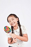 Smiling girl holding lollipop