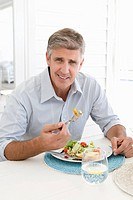 Portrait of mature man eating salad