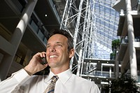 Businessman using mobilephone, smiling