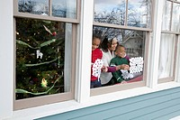 Mom & kids taping homemade snowflakes on window