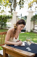 young woman writing at table outdoors