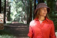 woman looking off at trailhead in forest