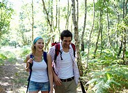 Young couple walking through woodland.