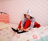 girl buckling shoe on bed