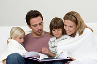 Family with two children 2_4 reading book together on sofa
