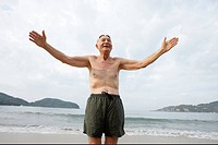Elderly man in swim trunks on beach with arms out