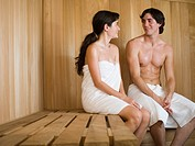 Close_up of a young couple looking at each other and sitting in a sauna