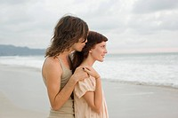 young couple holding on to each other on the beach