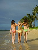Rear view of three teenage girls walking on the beach