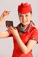 Chinese flight attendant applying make_up in compact mirror