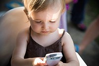 One year old baby studies a cell phone/PDA