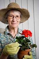 Portrait of an elderly woman holding a potted plant
