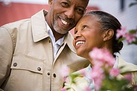 Close_up of a senior man and a senior woman smiling behind flowers