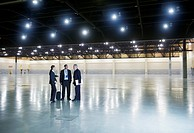 Business people talking in empty warehouse