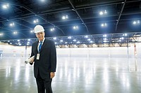 Caucasian businessman holding blueprints in empty warehouse