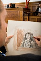 Close_up of a man drawing a sketch of a witness in a courtroom