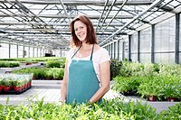 Germany, Bavaria, Munich, Mature woman in greenhouse with rocket plants