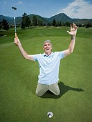 Man kneeling near a golf hole with his arms raised