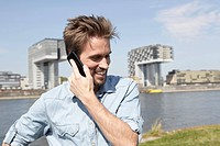 Germany, Cologne, Mid adult man talking on cell phone (thumbnail)