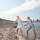Germany, Cologne, Young women skipping stones in river