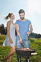 Germany, Cologne, Young couple grilling sausage and drinking beer (thumbnail)