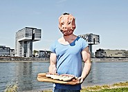Germany, Cologne, Young man with pig mask holding sausage
